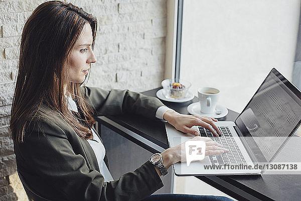 Seitenansicht einer Geschäftsfrau mit Laptop im Restaurant