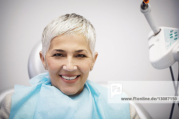 Portrait of smiling woman sitting on dentist's chair