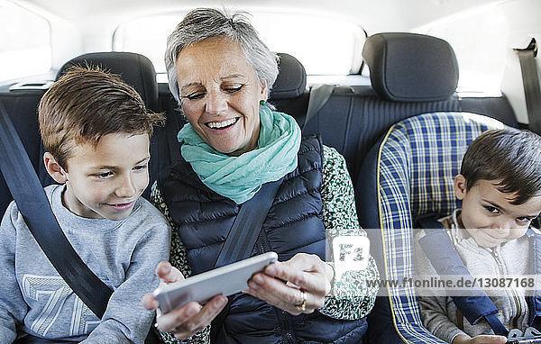 Glückliche ältere Frau mit Smartphone und Enkel im Auto