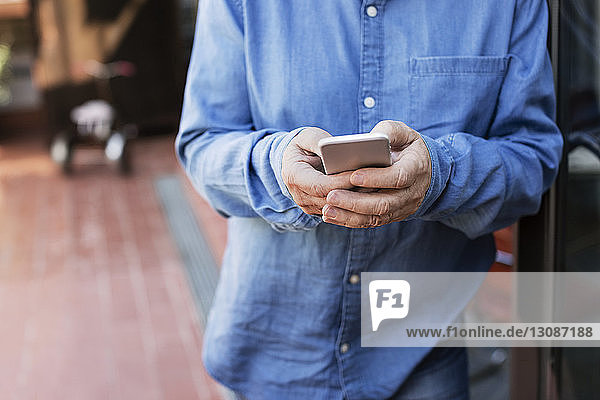 Midsection of senior man using smart phone at porch