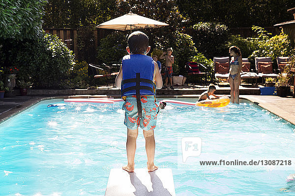 Boy standing on diving board
