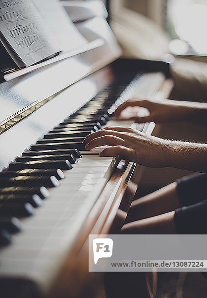 Cropped image of boy playing piano at home