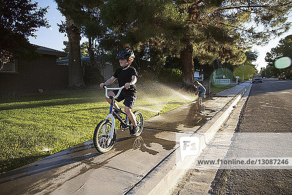 Boy riding bicycle on sidewalk while girl playing with sprinklers