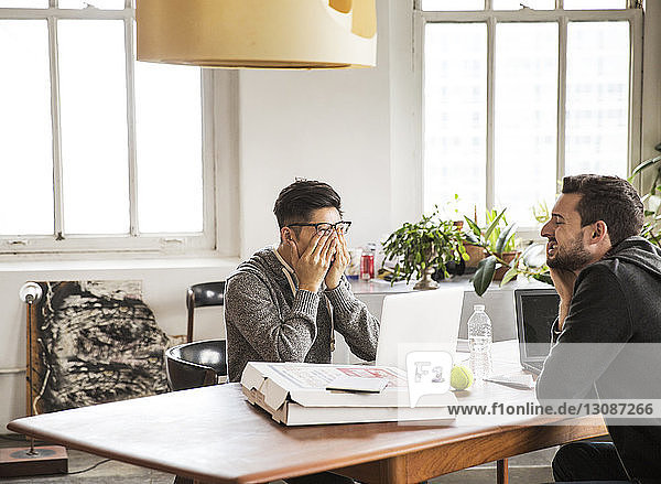 Tired businessmen with laptop computers at table in office