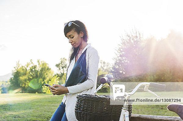 Lächelnde Frau telefoniert  während sie auf einer Parkbank sitzt