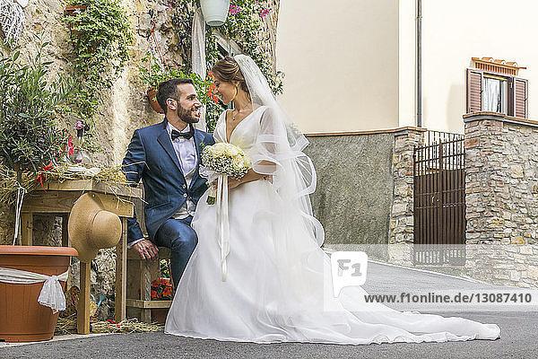 Romantisches frisch verheiratetes Paar  das sich in der Stadt auf einem Stuhl sitzend anschaut