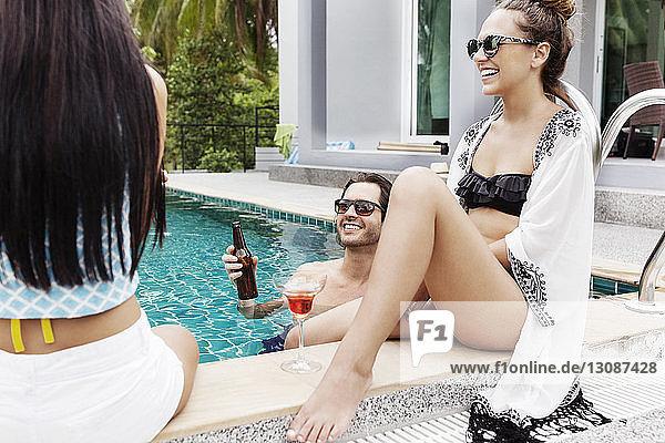 Fröhliche Freunde genießen Urlaub am Pool