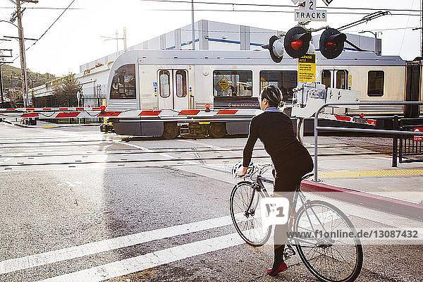 Rückansicht einer radfahrenden Geschäftsfrau  die auf den Zug wartet