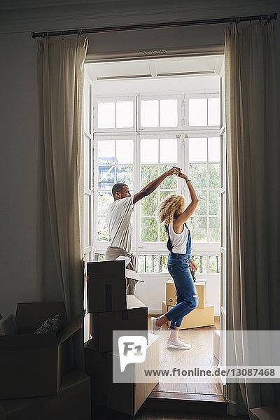 Couple dancing in new house seen through doorway