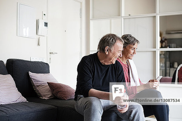 Happy sporty senior couple using smart phone while sitting on sofa at home