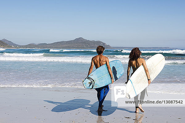 Rear view of friends carrying surfboards at beach during sunny day