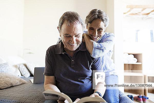 Fröhliches älteres Ehepaar liest Buch im Schlafzimmer