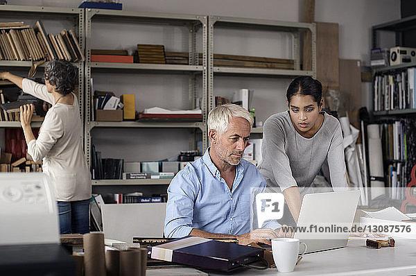 Multi-ethnic interior designers using laptop in creative office