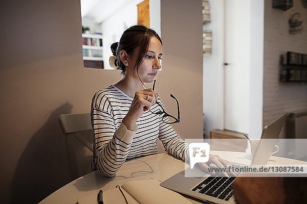 Concentrated woman holding eyeglasses while using laptop at table