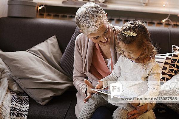 Großmutter und Enkelin benutzen einen Tablet-Computer  während sie auf dem Sofa sitzen