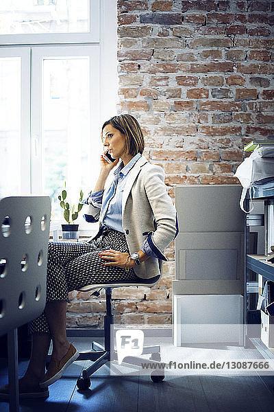 Geschäftsfrau telefoniert  während sie im Büro auf einem Stuhl sitzt