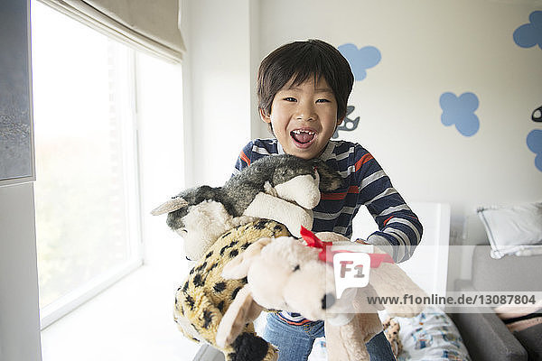 Happy boy playing with stuffed toys by window at home