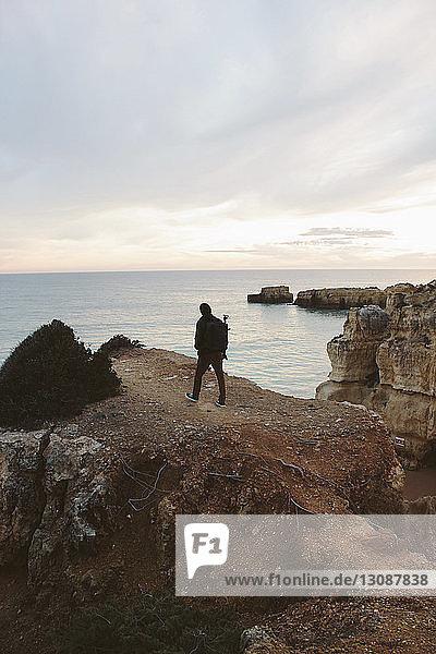 Rückansicht des auf einer Klippe am Meer stehenden Silhouettenmannes vor bewölktem Himmel bei Sonnenuntergang