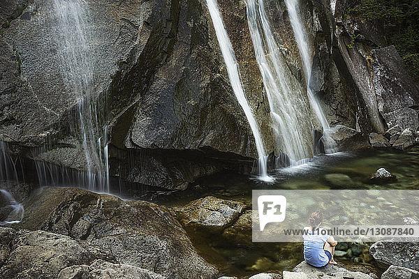 Rückansicht einer Frau  die auf einem Felsen vor Wasserfällen sitzt