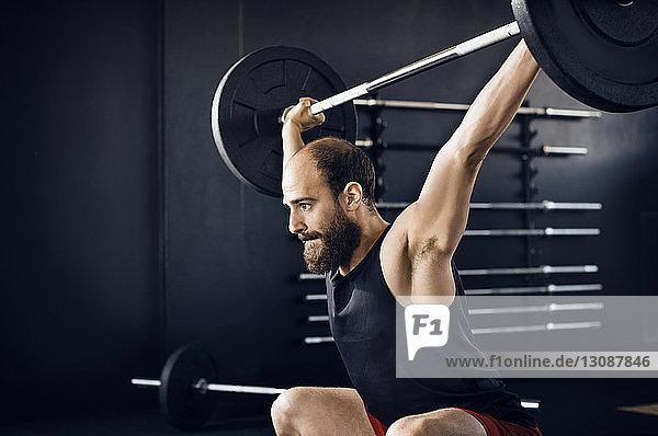 Entschlossener Athlet beim Hantelheben im Fitnessclub