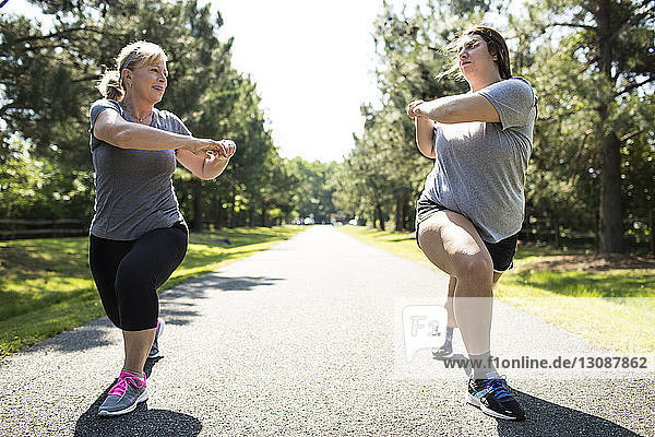 Mother and daughter exercising on footpath at park during sunny day
