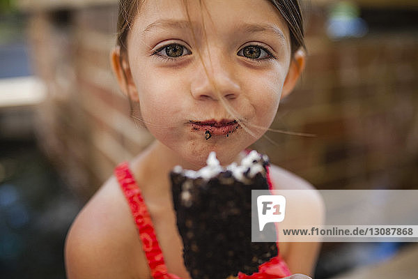 Portrait of happy girl eating chocolate popsicle