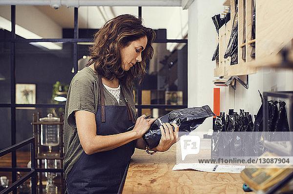 Seitenansicht eines weiblichen Geschäftsinhabers beim Lesen einer Kaffeebohnenpackung im Lager eines Cafés