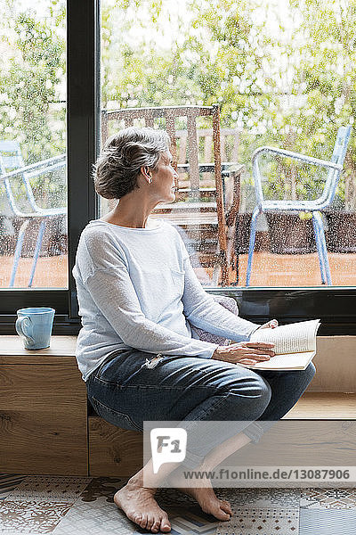 Thoughtful mature woman looking through window while holding book
