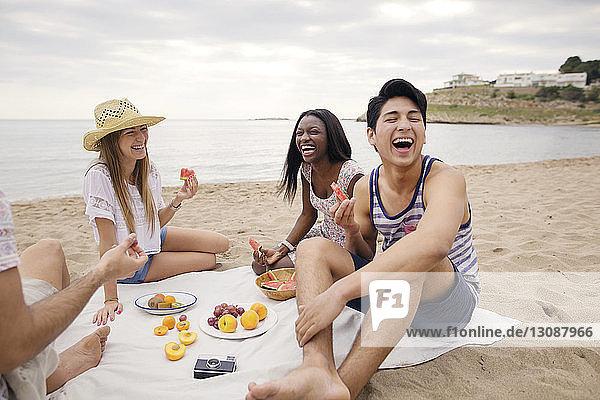 Fröhliche Freunde essen Früchte  während sie am Strand sitzen