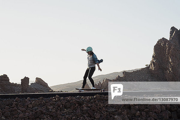 Skateboard fahrende Frau in voller Länge auf der Straße bei klarem Himmel
