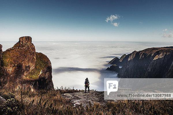 Rückansicht eines männlichen Wanderers  der auf einem Berg gegen den Himmel steht