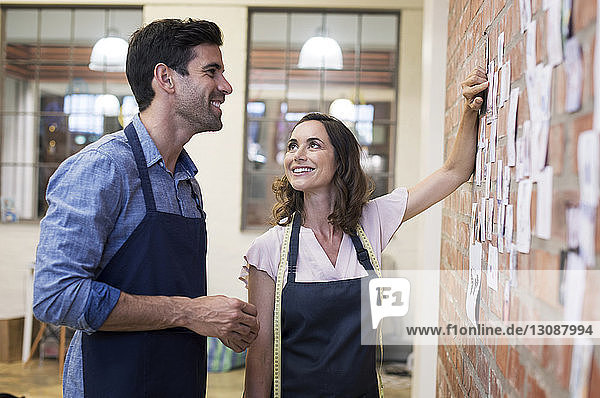 Fashion designer showing photographs on brick wall to colleague while standing at workshop