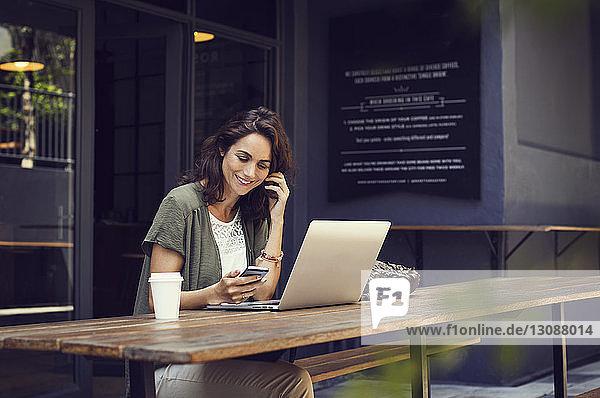Glückliche Frau  die ein Smartphone benutzt  während sie an einem Café-Tisch auf dem Bürgersteig sitzt