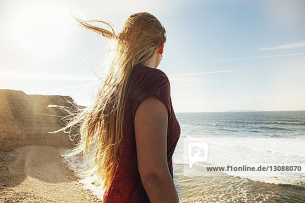 Side view of woman looking at view while standing at beach on sunny day