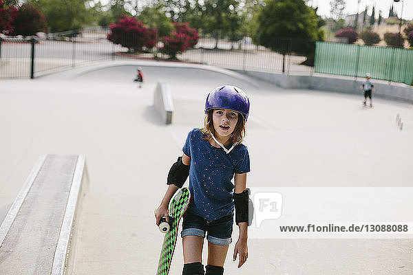 Girl carrying skateboard while walking at park