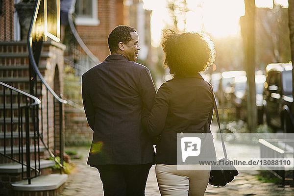 Rückansicht eines Paares  das bei Sonnenuntergang auf der Straße geht
