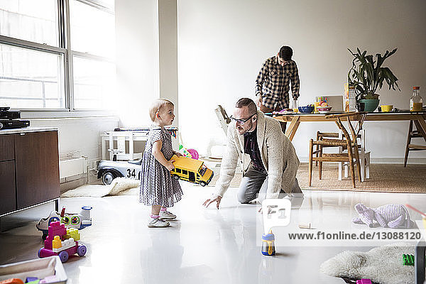 Father playing with daughter with partner working at table in brightly lit living room