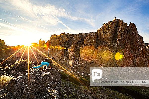 Frau streckt sich am sonnigen Tag im Smith Rock State Park auf Fels gegen Berge
