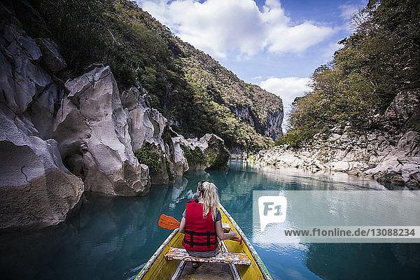 Rückansicht einer Frau  die in einem Boot auf einem Fluss inmitten von Bergen gegen den Himmel sitzt