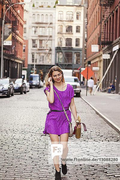 Lächelnde Frau geht auf gepflasterter Straße in der Stadt