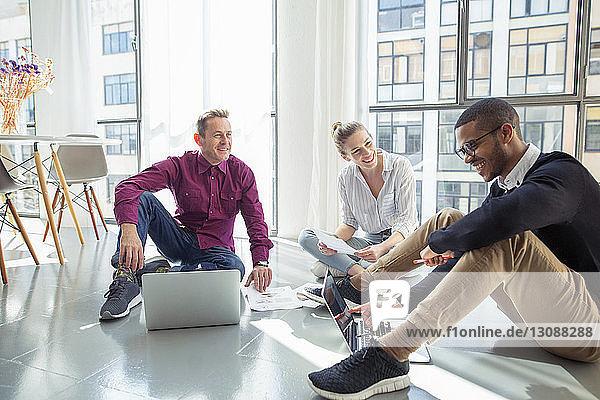 Geschäftsleute diskutieren sitzend mit Laptop-Computern am Fenster im Büro