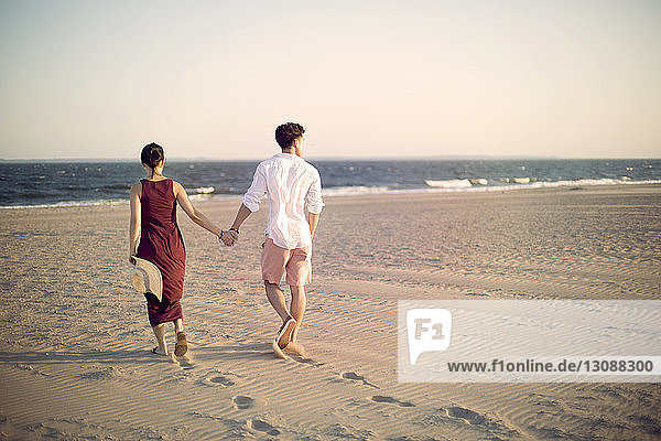 Rückansicht eines Paares  das sich beim Spaziergang am Strand im Sand an den Händen hält