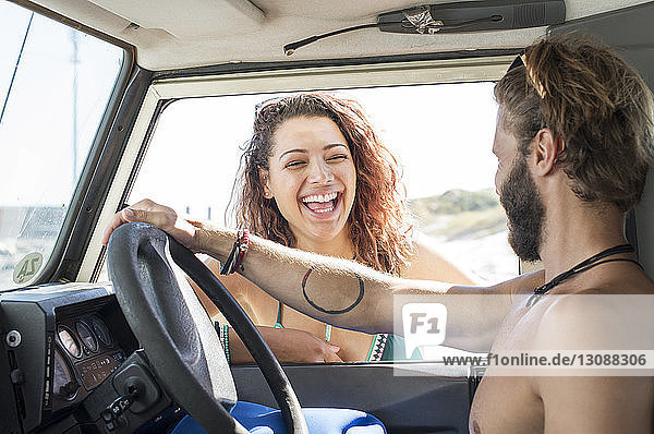 Happy woman talking to male friend sitting in off-road vehicle