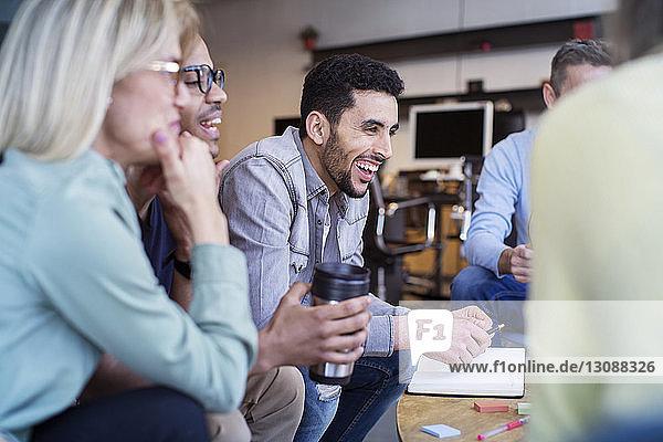 Fröhliche Kollegen diskutieren bei einer Besprechung im Büro