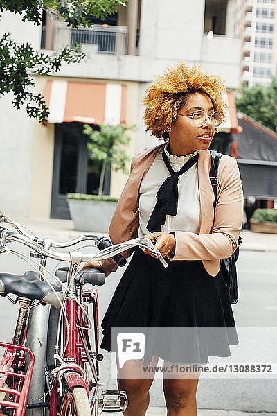 Frau hält Fahrräder in der Hand und schaut weg  während sie auf der Straße in der Stadt steht