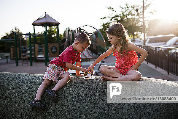 Siblings eating food in playground during sunset
