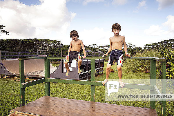 Boys sitting on railing