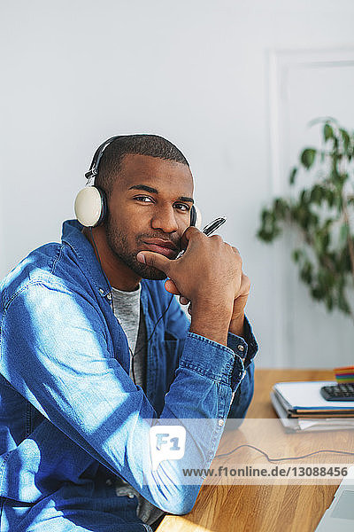 Side view portrait of man wearing headphones while sitting at wooden table