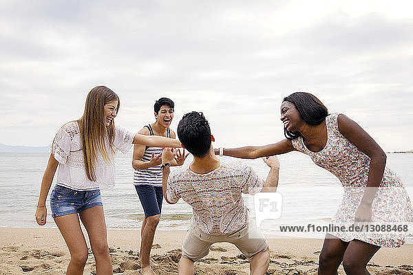 Mann geht unter den Armen der Frauen vorbei  während er am Strand gegen den Himmel spielt