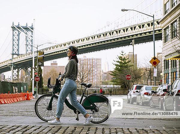 Seitenansicht einer Frau mit Fahrradmitfahrgelegenheit beim Gehen auf der Straße mit der Manhattan Bridge im Hintergrund